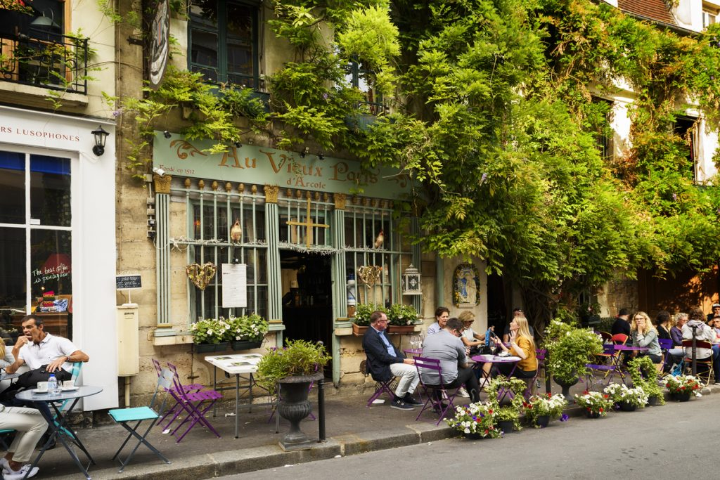 """Famous style of life in Paris, France with Bistrots and people on terraces. Here, this is """"The old Paris"""" traditional Bistrot on the Ile de la Cite in the spring time, near Notre Dame."""