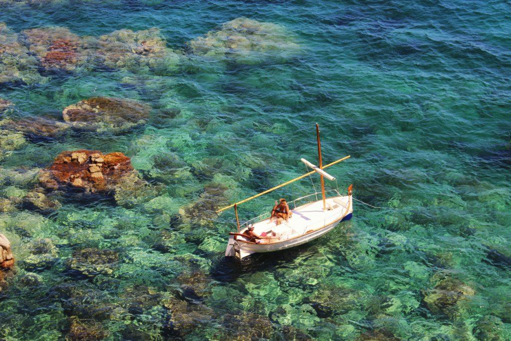 Enjoying the sun on a boat over the transparent green Mediterranean sea of Costa Brava