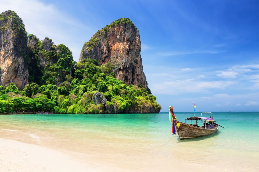Thai traditional wooden longtail boat and the beautiful sandy beach