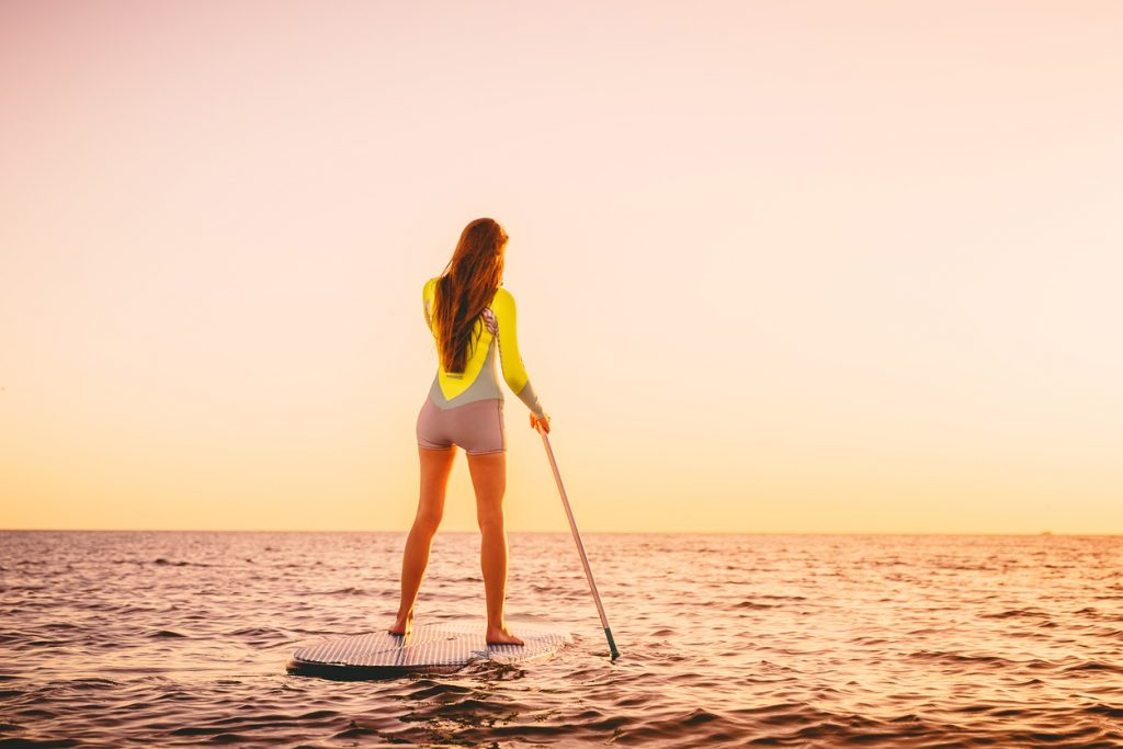 woman on stand up paddle board with beautiful sunset
