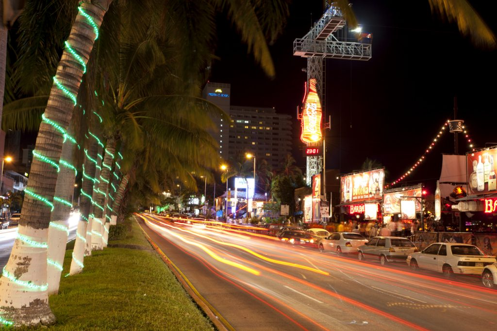 Enjoying the nightlife along the main coastal street (Av Costera Miguel Aleman) in Acapulco, Mexico. This street is lined with bars, restaurants, shops and hotels. the large tower with the Coke-cola neon signs a Bungy jump tower.
