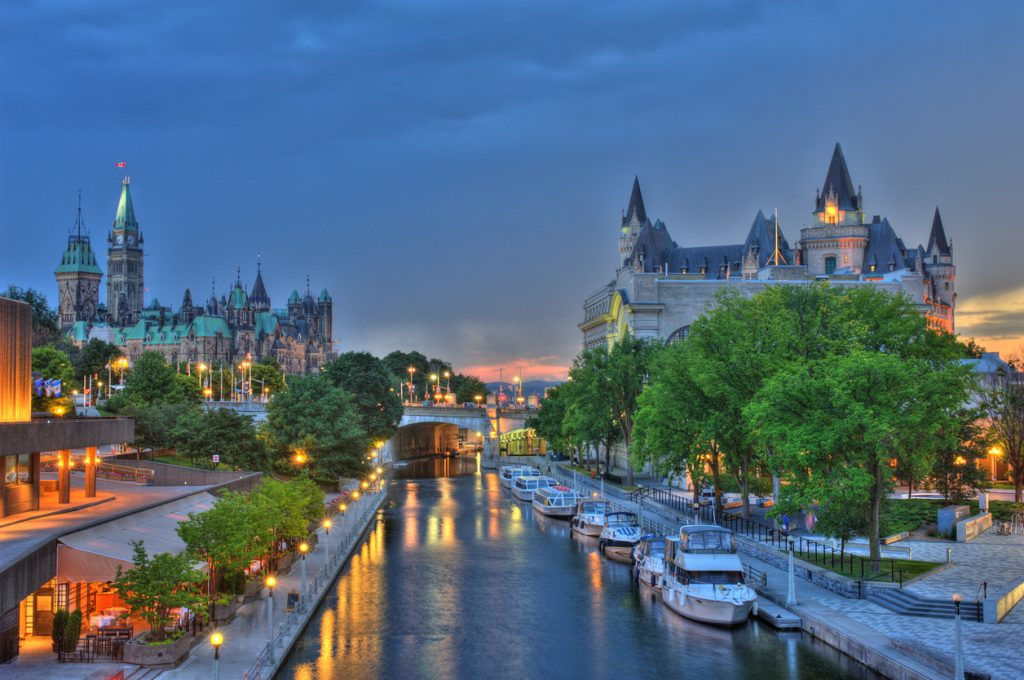 Ottawa at sunset with storm clouds advancing. Featuring Parliament Buildings, Rideau Canal a UNESCO world heritage site, Chateau Laurier Hotel, National Art Gallery and National Conference Centre. Boats docked along Rideau Canal.