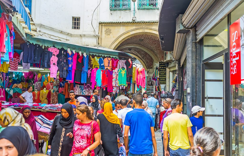 The crowded clothes bazaar stretches along the narrow Kasbah street in Medina