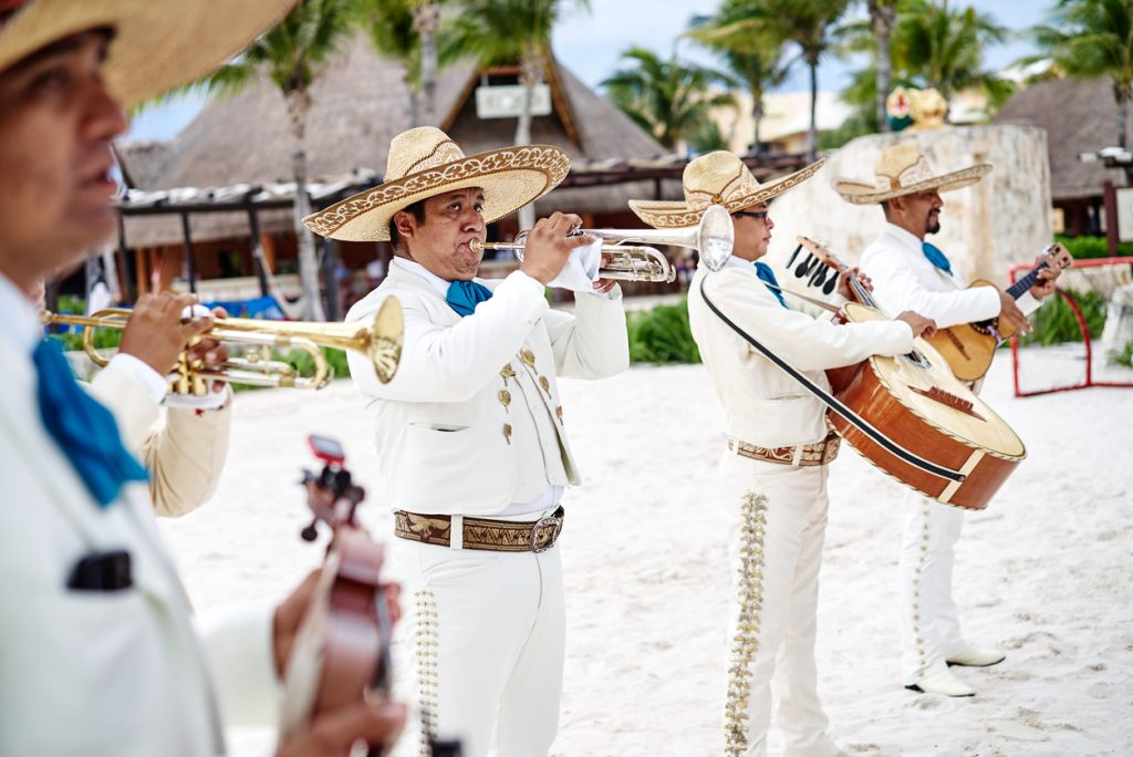 A group of traditional Mexican music band playing trumpet, classical guitar on the beach for beach wedding ceremony in Cancun, Yucatan, Mexico