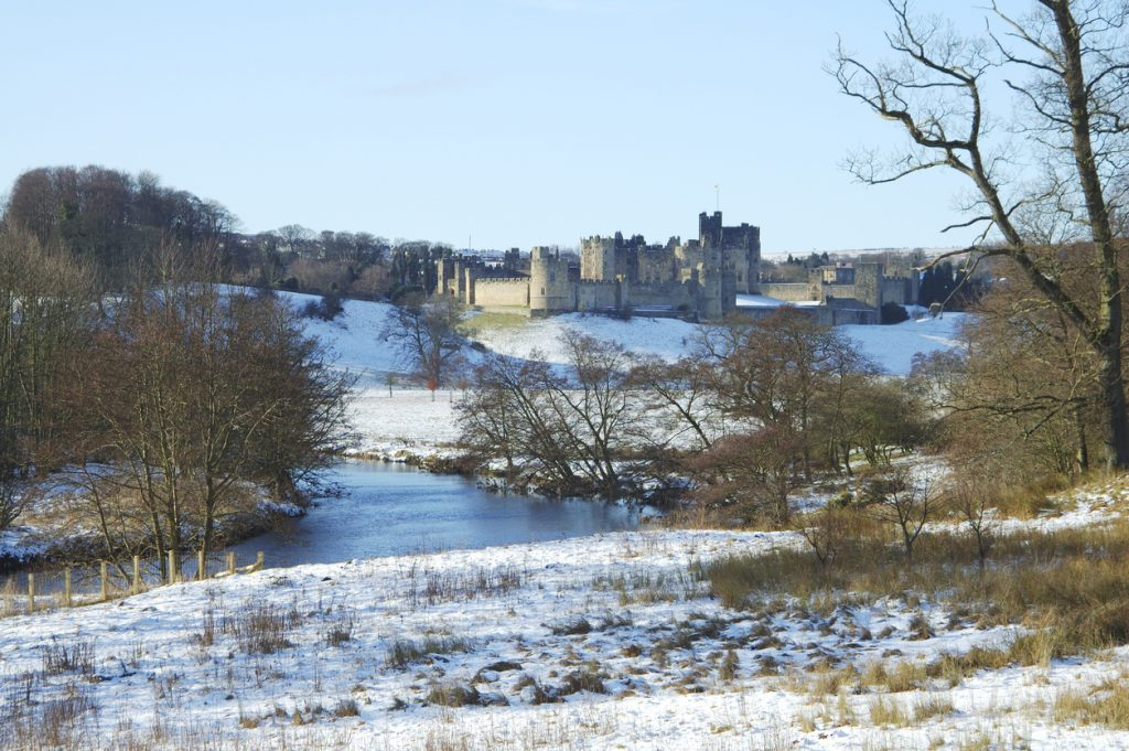 View to Alnwick castle in snow scene with river Aln, blue sky and sunshine.