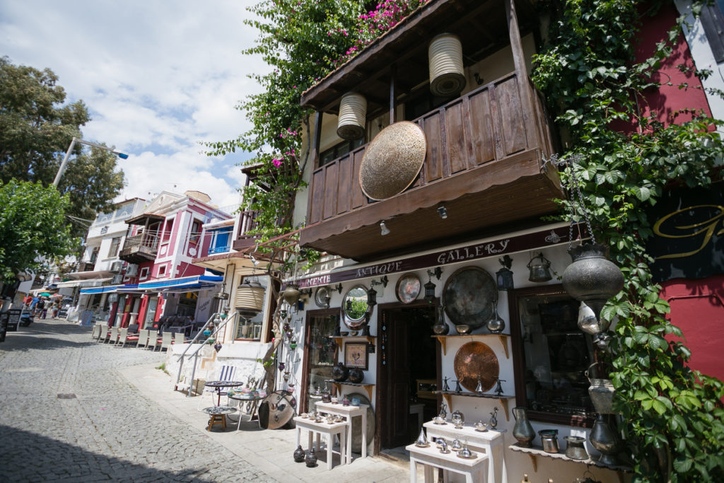 Antique shop decorated with metal trays, jugs, lanterns and other souvenirs on cobblestone paved narrow streets of Kalkan