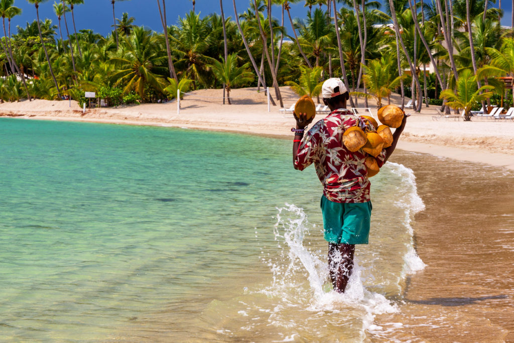 Caribbean coconut saler in walking in a tropical beach of Dominican Republic