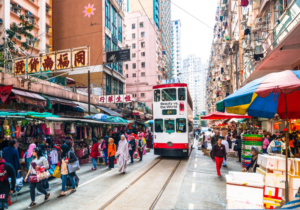 A Hong Kong tram squeezes past shoppers and stalls at the Chun Yueng Street Market in North Point, Hong Kong