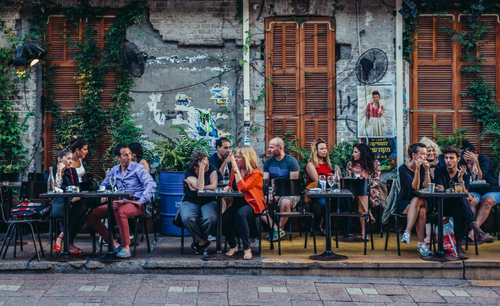 People sit at tables outside the restaurant at Rothschild Boulevard in Tel Aviv
