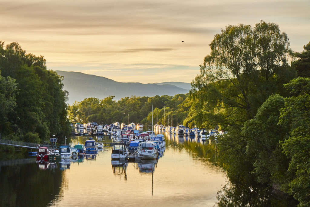 Scenic sunset view of Balloch harbour near Loch Lomond with floating boats reflected in river Leven, Scotland