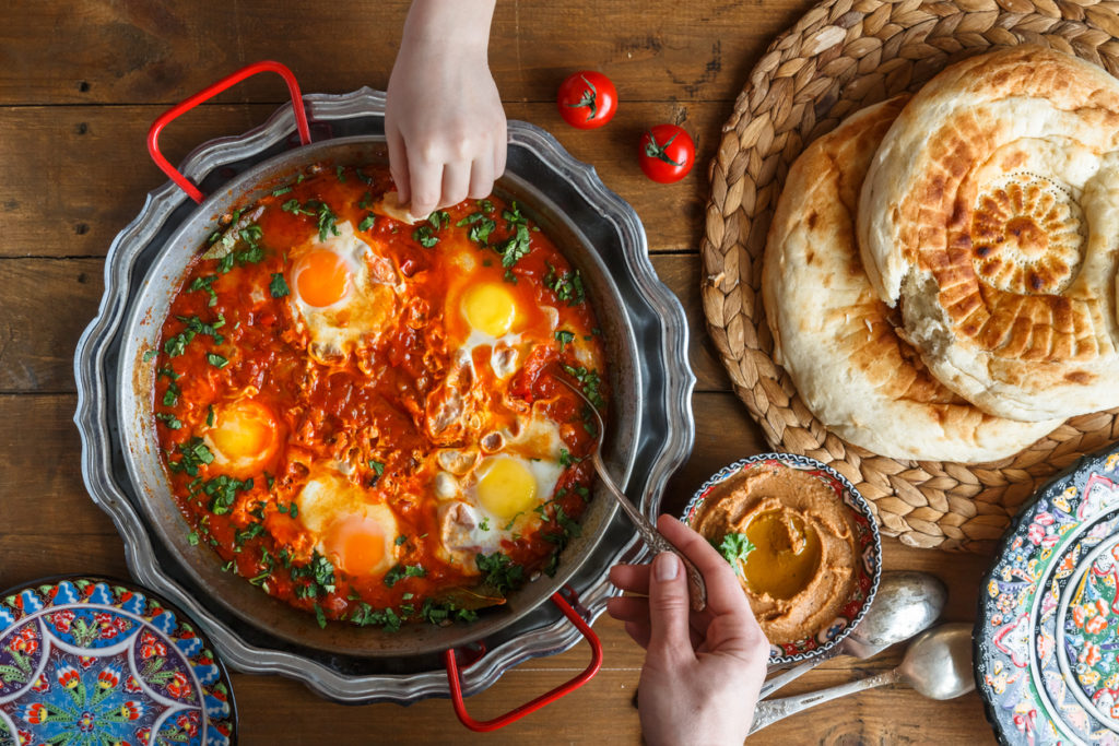Tasty family breakfast with shakshuka, bread and hummus.