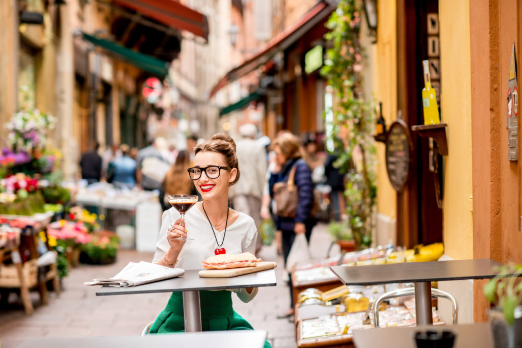 Sitting at the cafe with shakerato coffee and panini outdoor on the famous street with local food markets in Bologna city.