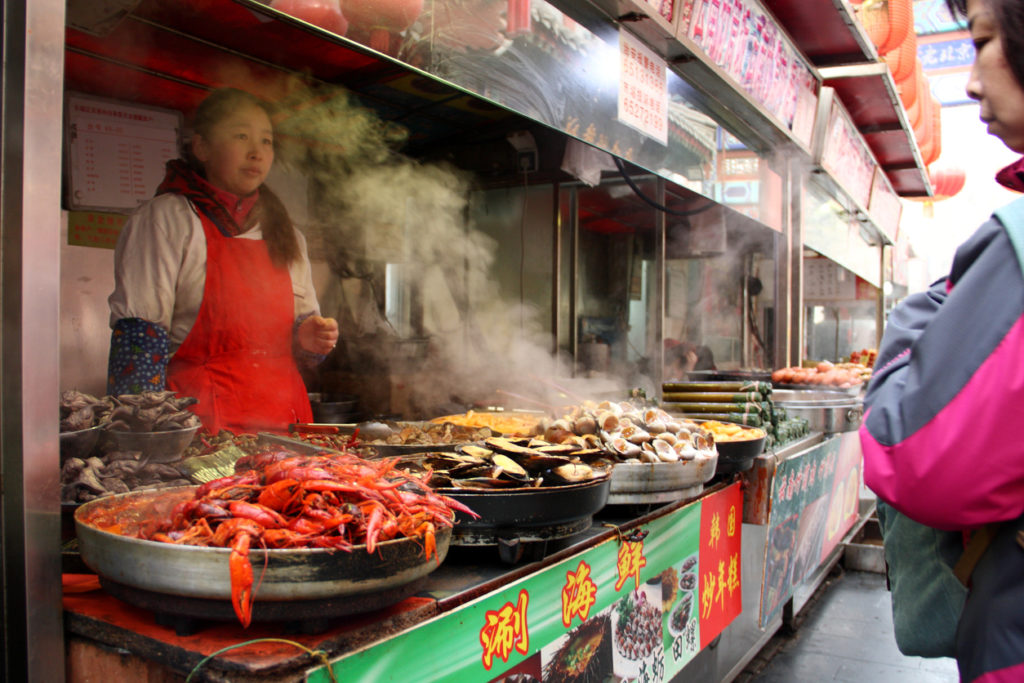 Vendors sell Chinese snacks on the 'food and drink' street of the shopping area Wangfujing