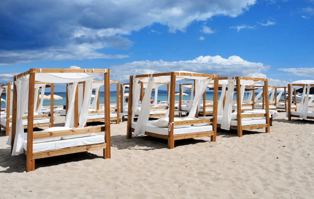 Beds and sunloungers in a beach club in a white sand beach in Ibiza, Spain