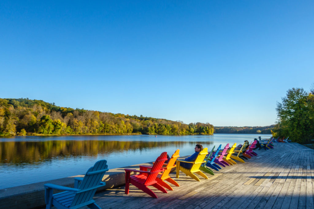Brightly colored adirondack chairs along a river with trees in background