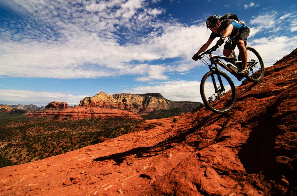 Mountain biker going downhill on slickrock in Sedona, Arizona