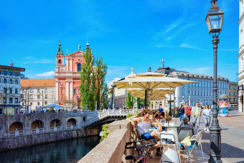 People at sidewalk cafe on Triple bridge Ljubljanica River Ljubljana