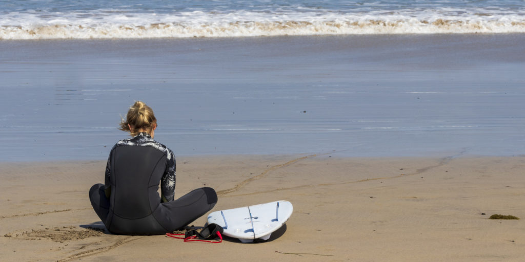 Surfer girl sitting at La Caleta beach. Lanzarote.