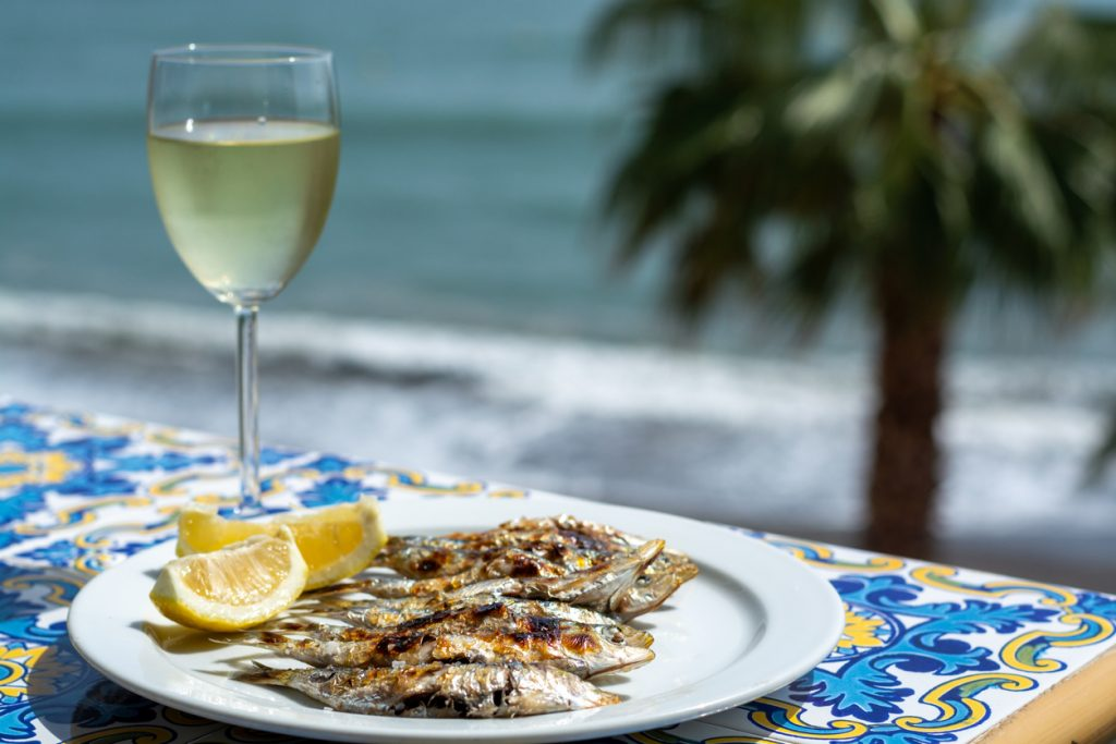 Sardines espeto, Marbella style fish on stick barbecue prepared on olive tree firewoods on beach served with white wine