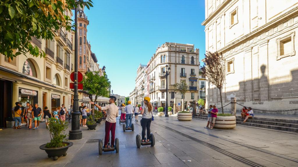 Tourists on segways at Av. de la Constitucion in the historic centre of Seville, Andalusia, Spain