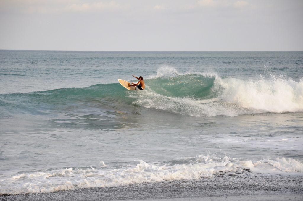 A surfer rides a wave at Jaco Beach