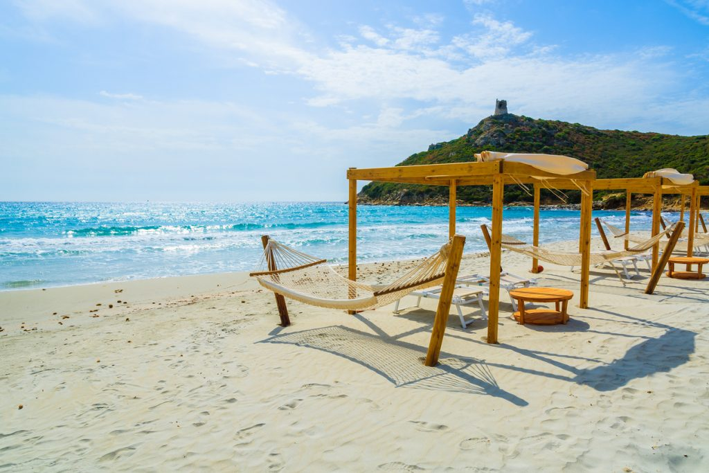 Hammocks and sun chairs on beach in Porto Giunco, Villasimius, Sardinia island, Italy
