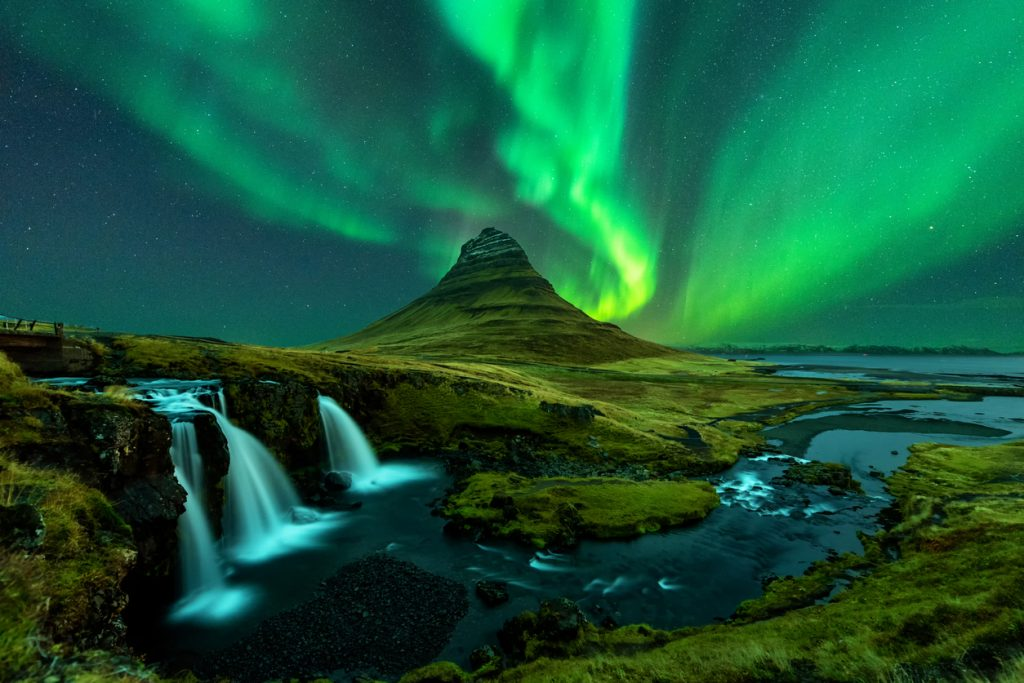 Northern lights appear over Mount Kirkjufell with kirkjufellfoss waterfall in Iceland.