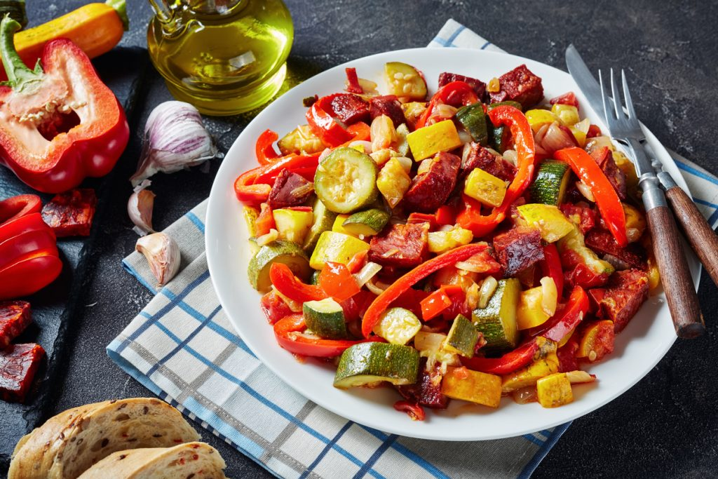 Pisto - Spanish vegetable stew with fried chorizo sausages served with sliced bread