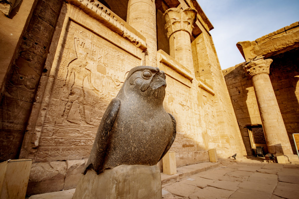 Sunset at Temple of Edfu with the statue of falcon God Horus