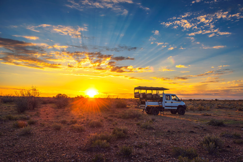 Safari vehicle stops in the Kalahari desert for a dramatic sunset