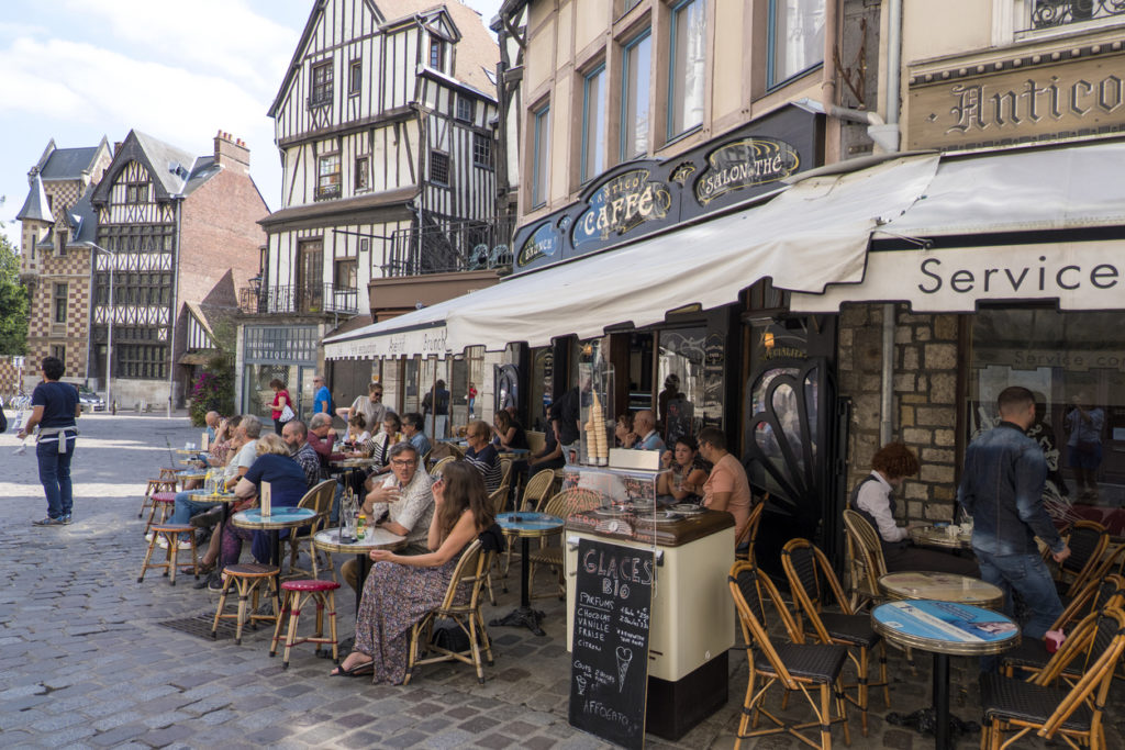Residents of the city and tourists relax in a cafe on a street in the center of Rouen. Normandy,