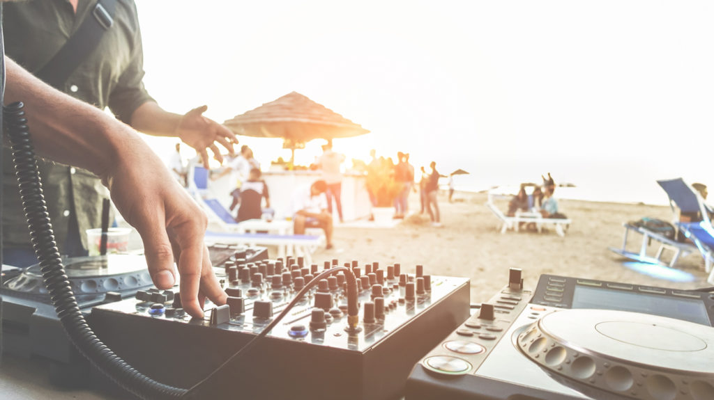 DJ mixing at sunset beach party