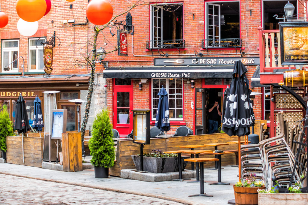 Lower old town cobblestone street called Sous le Fort with restaurants and hanging colorful decorations