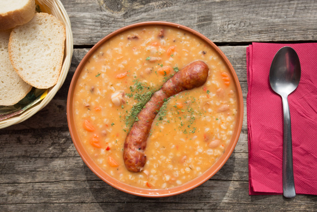 Barley soup with traditional krainer sausage in bowl