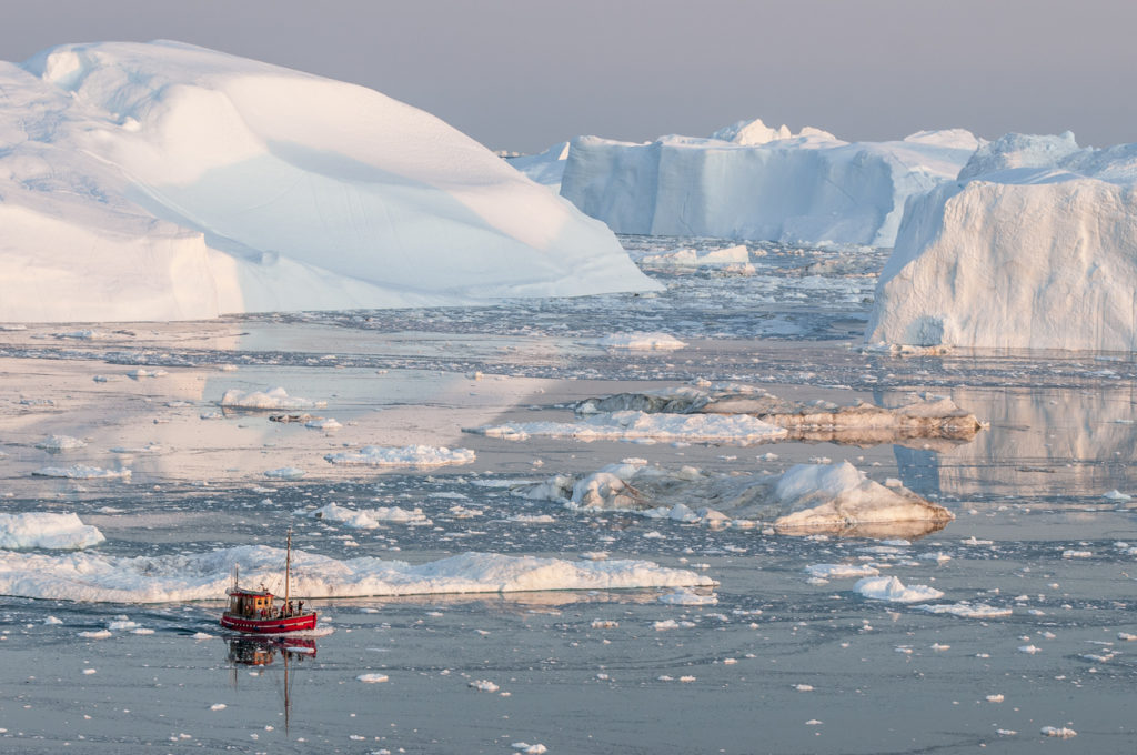 Boat among iceberg in Greenland