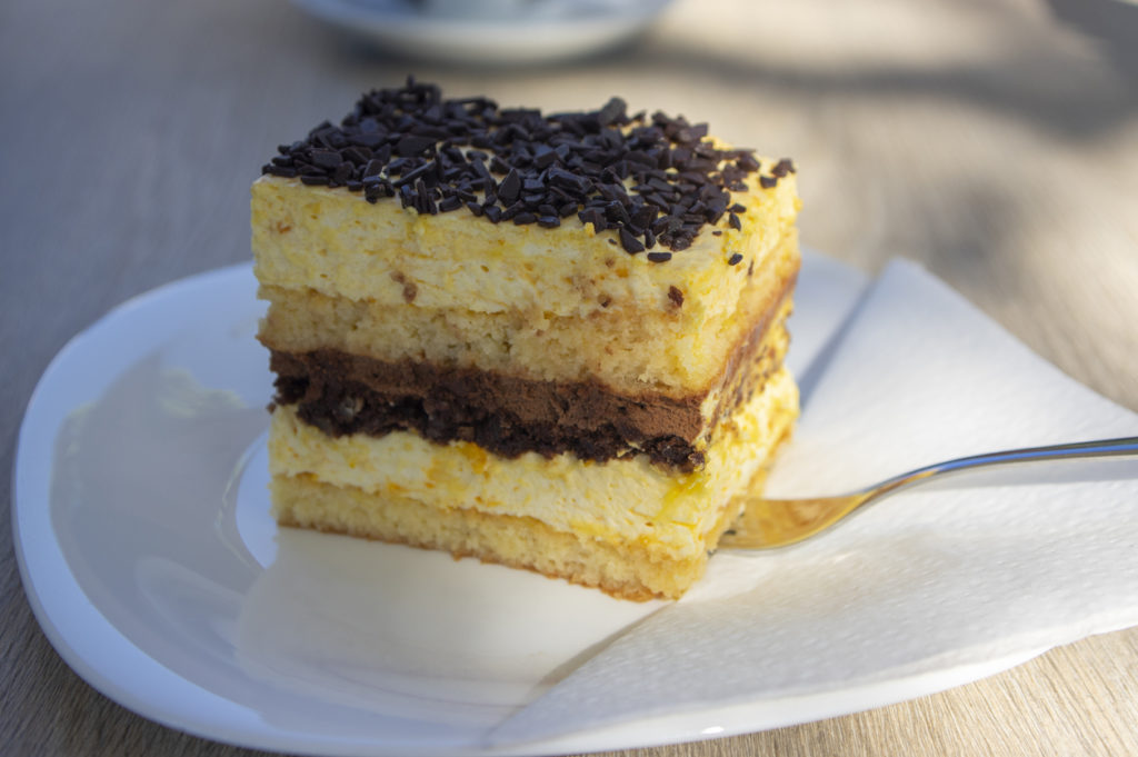 Delicious Slovenian cake on white plate called Izolanka, very tasty dessert with chocolate and orange