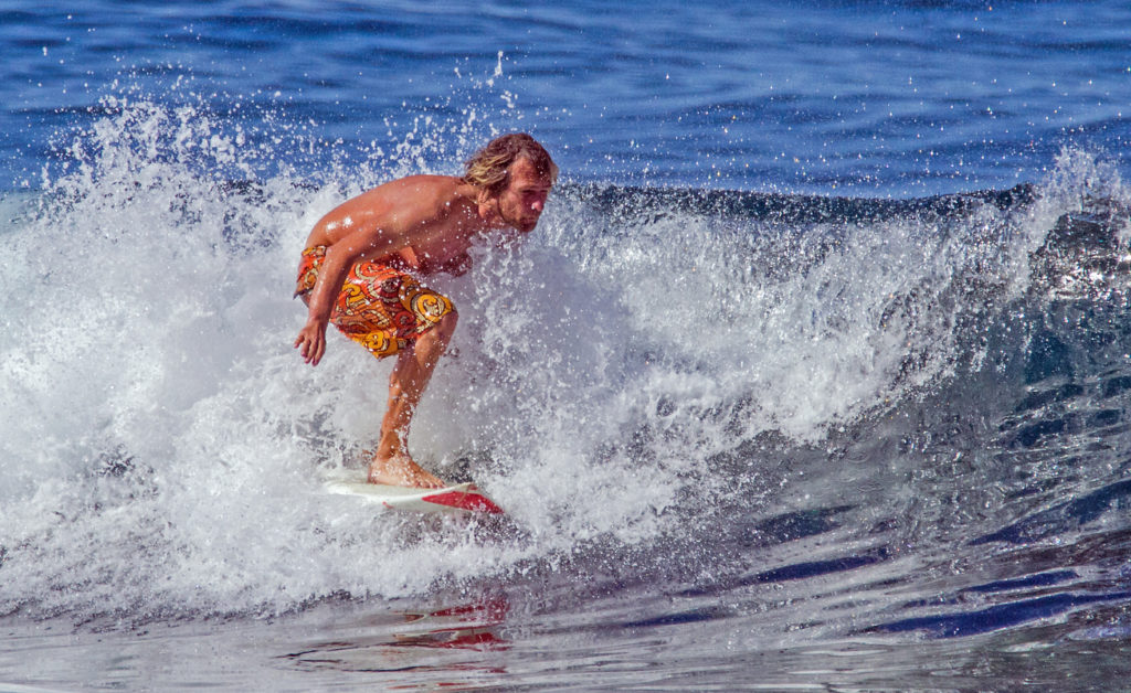A surfer rides a wave at the beach in Playa De Las Americas, Tenerife.