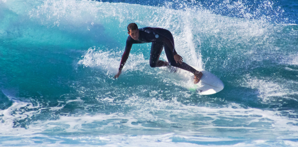Surfer cuts a carve in Playa De Las Americas, Tenerife
