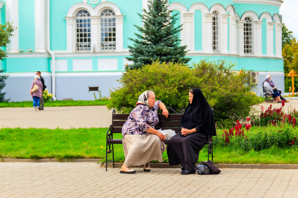 Orthodox nun and a pilgrim sitting on a bench