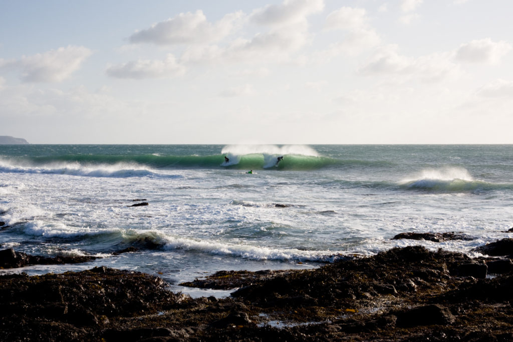 Surfers ride a wave at a reef in Porthleven