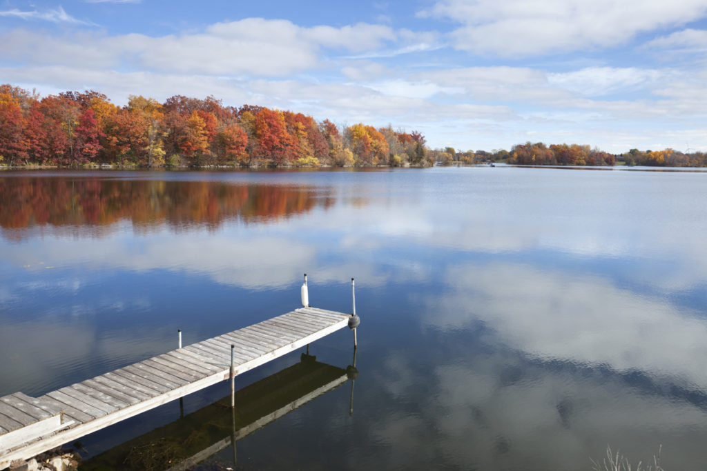 Calm Minnesota lake with dock and trees in Fall